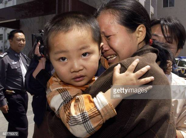 Woman cries as she is reunited with her son, one of the children rescued from a group of human traffickers in Zhengzhou, central China's Henan...