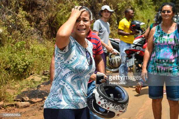 A woman cries as she sees the damages caused by the mining waste a day after the collapse of a dam from an ironore mine belonging to Brazil's mining...