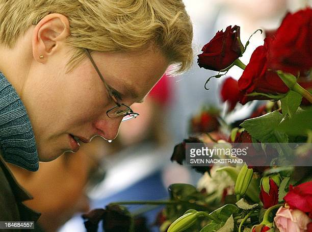 A woman cries as she signs the book of condolences for Foreign Minister Anna Lindh outside the NK department store in Stockholm 19 September 2003...