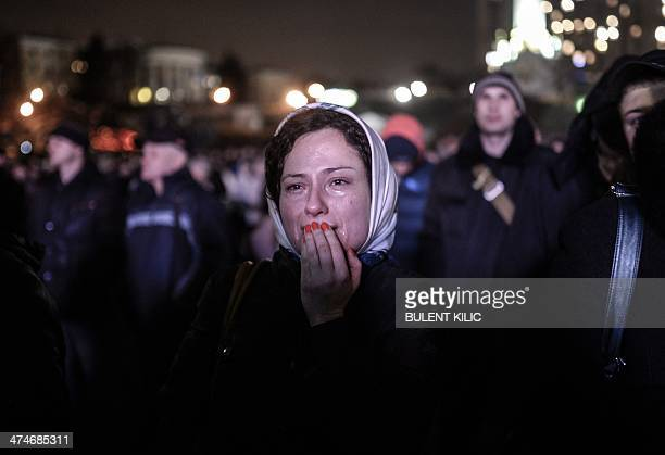 A woman cries as she stay on Kiev's Independence Square on February 25 2014 Ukraine issued an arrest warrant Monday for ousted president Viktor...