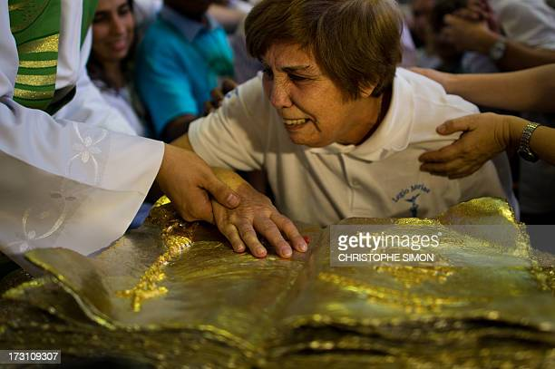 A woman cries as she touches a relic after a mass officiated by Cardinal Stanislaw Rylko to celebrate the arrival in Brazil of the relics of blessed...