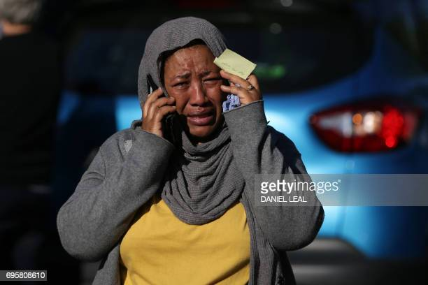 A woman cries as she tries to locate a missing relative suspected of being affected by the massive fire that engulfed Grenfell Tower a residential...