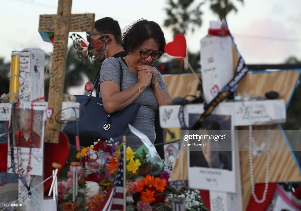 A woman cries as she visits a makeshift memorial setup in front of Marjory Stoneman Douglas High School in memory of the 17 people that were killed on February 14, on February 21, 2018 in Parkland, Florida. Police arrested 19-year-old former student Nikolas Cruz for killing 17 people at the high school.