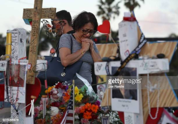 A woman cries as she visits a makeshift memorial setup in front of Marjory Stoneman Douglas High School in memory of the 17 people that were killed...
