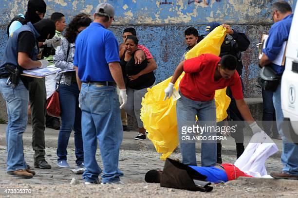 A woman cries as the corpse of her son a supporter of Olimpia football team is covered by forensic personnel after he was shot dead as he was going...