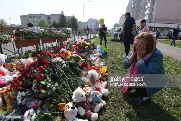 Woman cries at a makeshift memorial for victims of the shooting at School No. 175 in Kazan on May 12, 2021. - At least nine people, most of them...