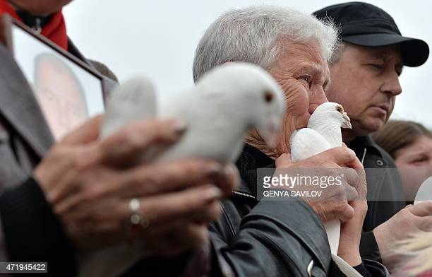 Woman cries before releasing a white dove during a pro-Russian meeting at Kulikove Pole Square in Odessa, southern Ukraine, on May 2, 2015 in memory...