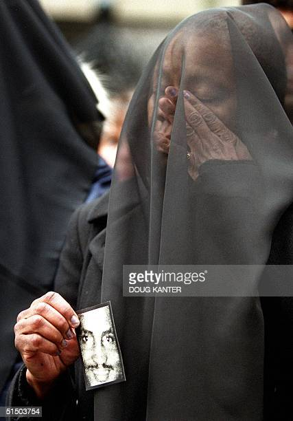 A woman cries below a black veil while holding a picture of slain African immigrant Amadou Diallo at a rally in New York 27 February 2000 Hundreds...