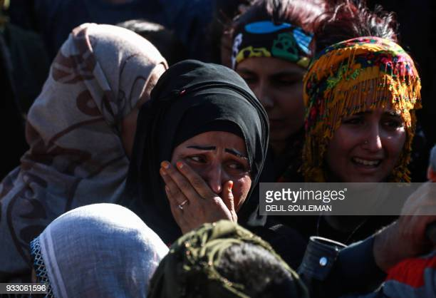 A woman cries during the funeral of People's Protection Units fighters in the northeastern Syrian city of Qamishli on March 17 who were killed while...