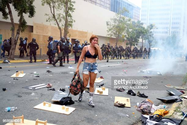 TOPSHOT A woman cries in front of a riot police line after being affected by tear gas was deployed during a May Day protest against pension cuts...