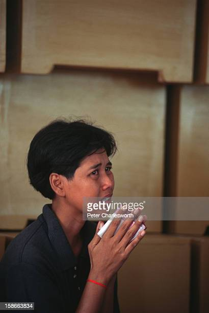 A woman cries in front of a stack of coffins at the funeral of an AIDS victim at the Buddhist Temple called Wat Pra Bat Nam Pu The temple is a refuge...