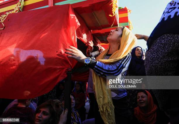 A woman cries next to a coffin during the funeral of People's Protection Units fighters in the northeastern city of Qamishli on March 17 who were...