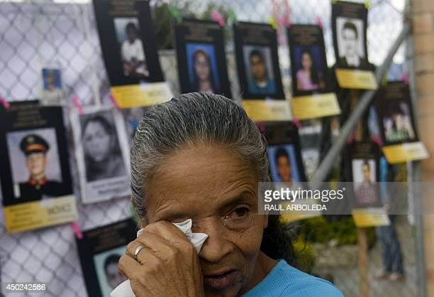 A woman cries next to the pictures of missing people at 'La Escombrera' a dumping ground for construction materials at the Commune 13 neighbourhood...