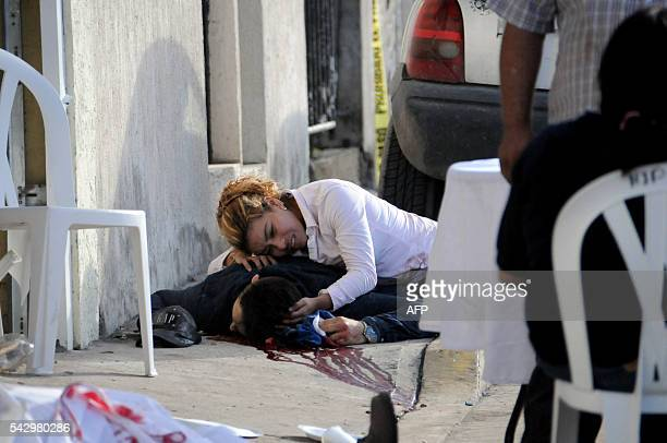 A woman cries on June 25 2016 over the body of a relative who was shot dead on the eve when unknown gunmen arrived at a party and opened fire in...