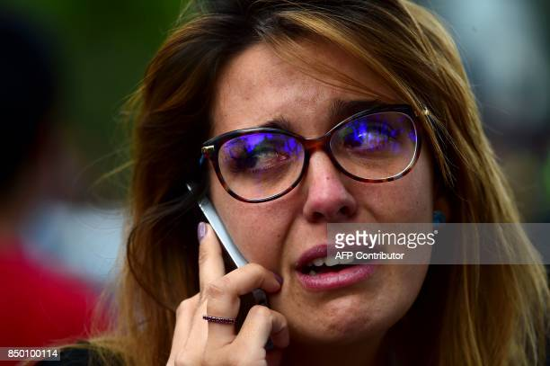 A woman cries on the phone as the search for survivors continues in Mexico City on September 20 2017 a day after a strong quake hit central Mexico A...