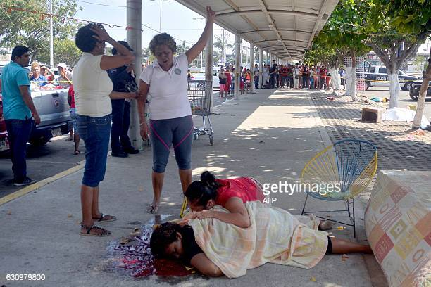 TOPSHOT A woman cries over the corpse of her family member murdered in the parking lot of a shopping center in Acapulco Guerrero State Mexico on...