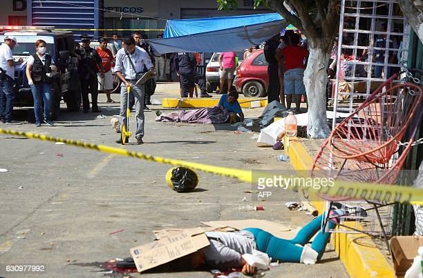 A woman cries over the corpse of her murdered family member while forensic personnel work at the scene of the crime in the parking lot of a shopping...