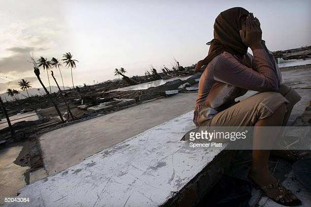 A woman cries while sitting on the remains of her home that was destroyed in the tsunami January 21 2005 in Banda Aceh Indonesia More than three...