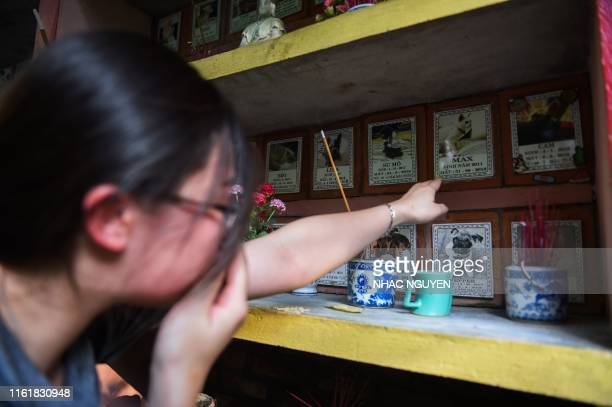 A woman cries while touching the plague of her cat at Te Dong Vat Nga pagoda which means all lives are equal a pet cemetary in Hanoi on August 15...