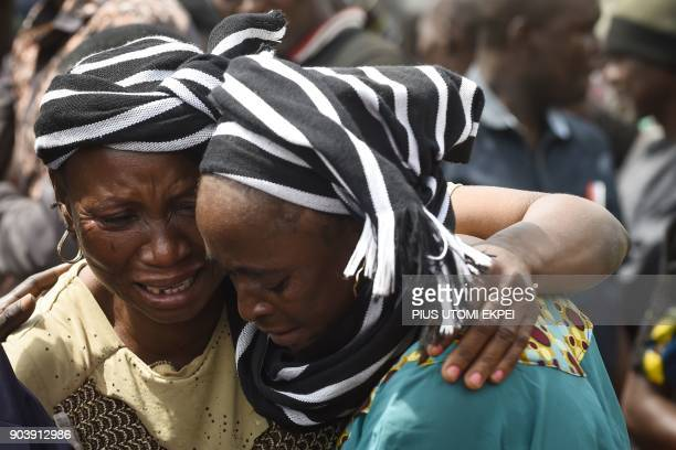 A woman cries while trying to console a woman who lost her husband during the funeral service for people killed during clashes between cattle herders...