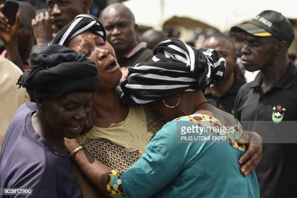 TOPSHOT A woman cries while trying to console a woman who lost her husband during the funeral service for people killed during clashes between cattle...