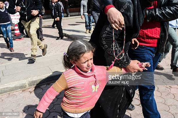 TOPSHOT A woman cries with her children after her injured husband arrived from northern Syria in front of Kilis hospital in southcentral Turkey on...