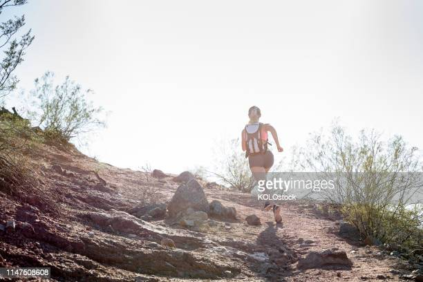Woman cross country running in the desert