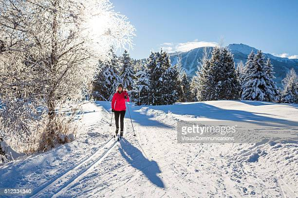 Woman cross country skiing on sunny day.