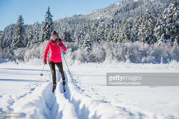 woman cross country skiing on sunny day. - langlaufen stockfoto's en -beelden