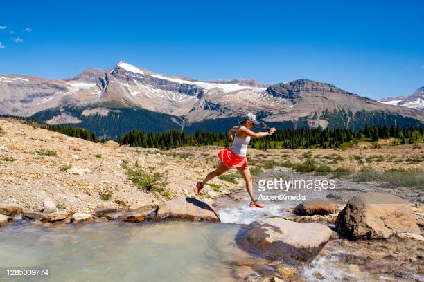 woman cross-country runner jumps over a high mountain stream - forward athlete stock pictures, royalty-free photos & images