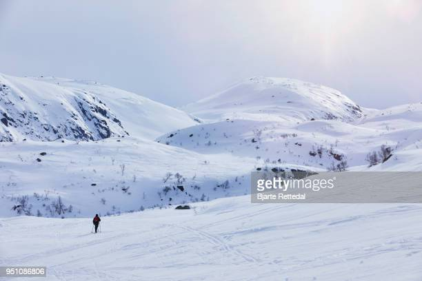 Woman cross-country skiing through mountain landscape