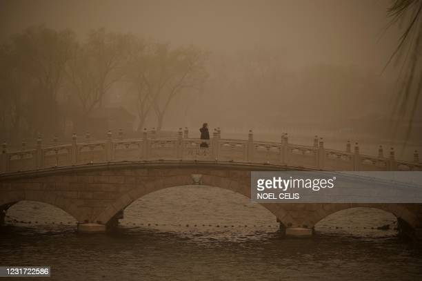 Woman crosses a bridge at Houhai lake during a sandstorm in Beijing on March 15, 2021.