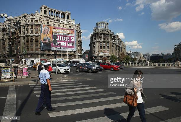 A woman crosses a busy street in the city center on September 6 2013 in Bucharest Romania While the country's economic output has risen significantly...