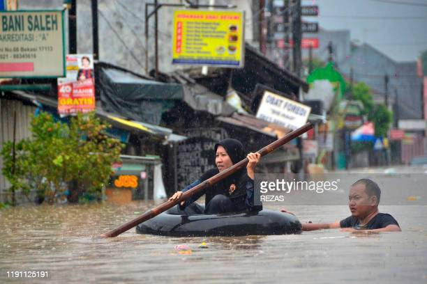A woman crosses a flooded area in an inflated innertube after rain all night caused local flooding in Bekasi West Java on January 1 2020 Storms...