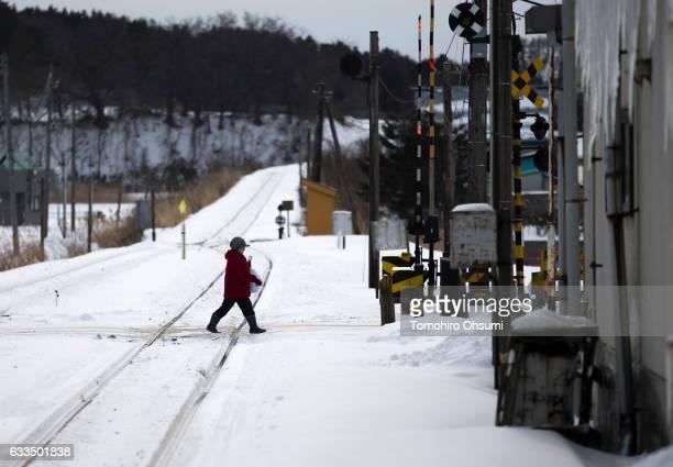 A woman crosses a rail track after a Tsugaru Railways train departs a train station on February 1 2017 in Aomori Japan The Tsugaru Railways...