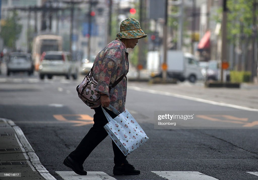 A woman crosses a road in Okayama, Japan, on Tuesday, May 21, 2013. The Bank of Japan, forecast to maintain plans for expanded monetary easing at a meeting ending on May 22, is targeting 2 percent inflation in two years after more than 10 years of entrenched deflation. Photographer: Tomohiro Ohsumi/Bloomberg via Getty Images