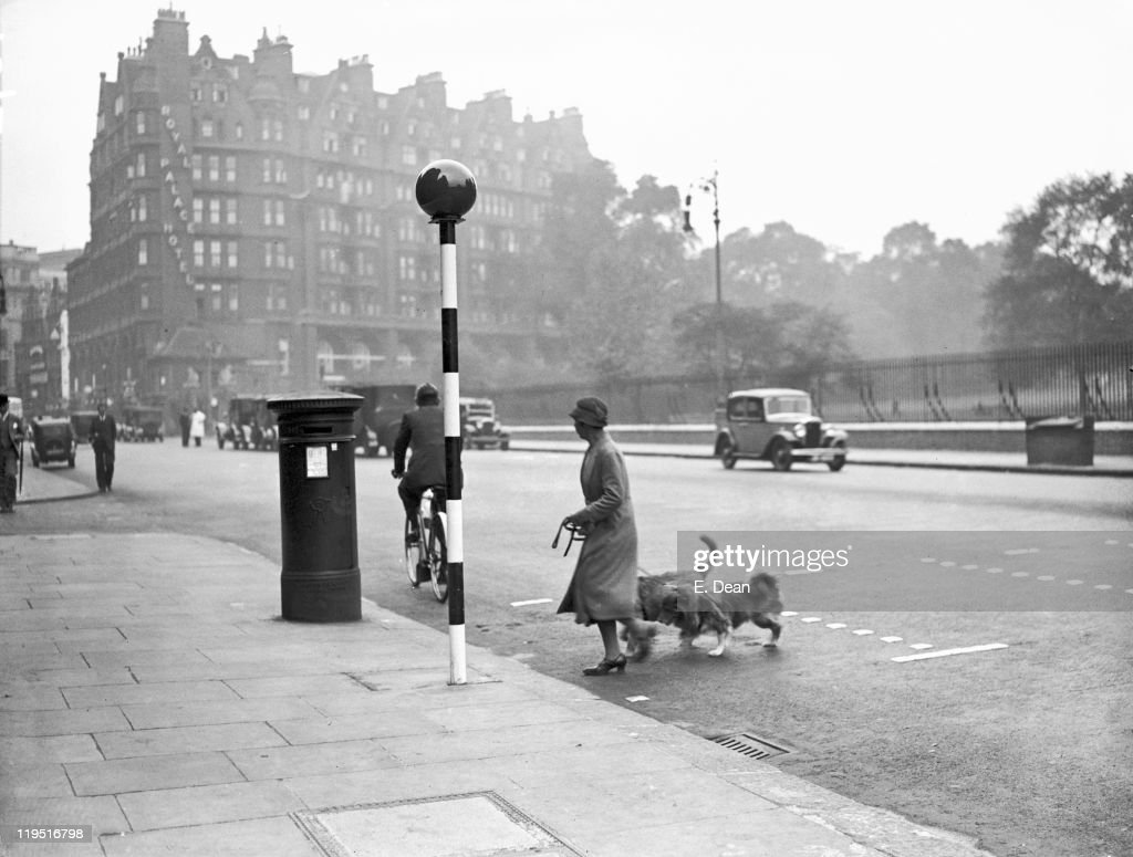 A woman crosses a road near one of the newly-introduced belisha beacons, Kensington, London, 18th September 1934. The crossing is also marked by metal studs in the road surface.
