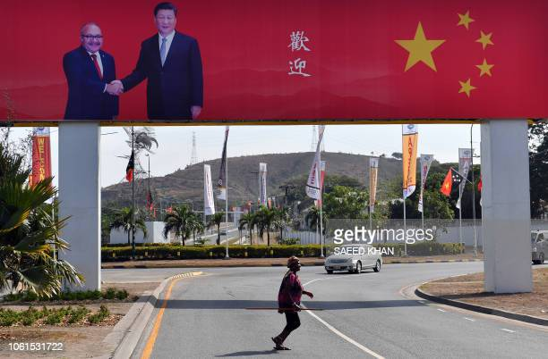 A woman crosses a road with a billboard featuring Papua New Guinea Prime Minister Peter O'Neill shaking hands with China's President Xi Jinping and a...