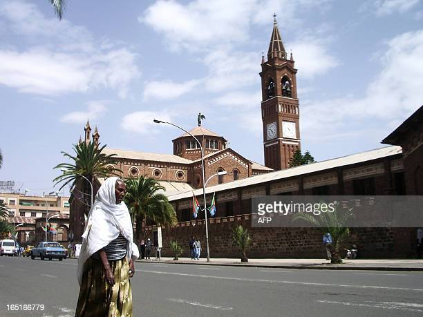 A woman crosses a street adjacent to the Cathedral and Catholic Mission compound in Asmara 03 July 2007 Frustrated avantgarde architects from an...