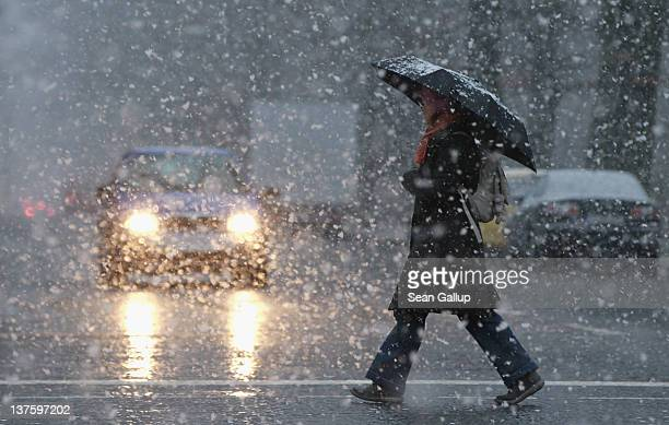 A woman crosses a street under a sudden heavy snowfall on January 23 2012 in Berlin Germany Today was the first day the city has seen significant...