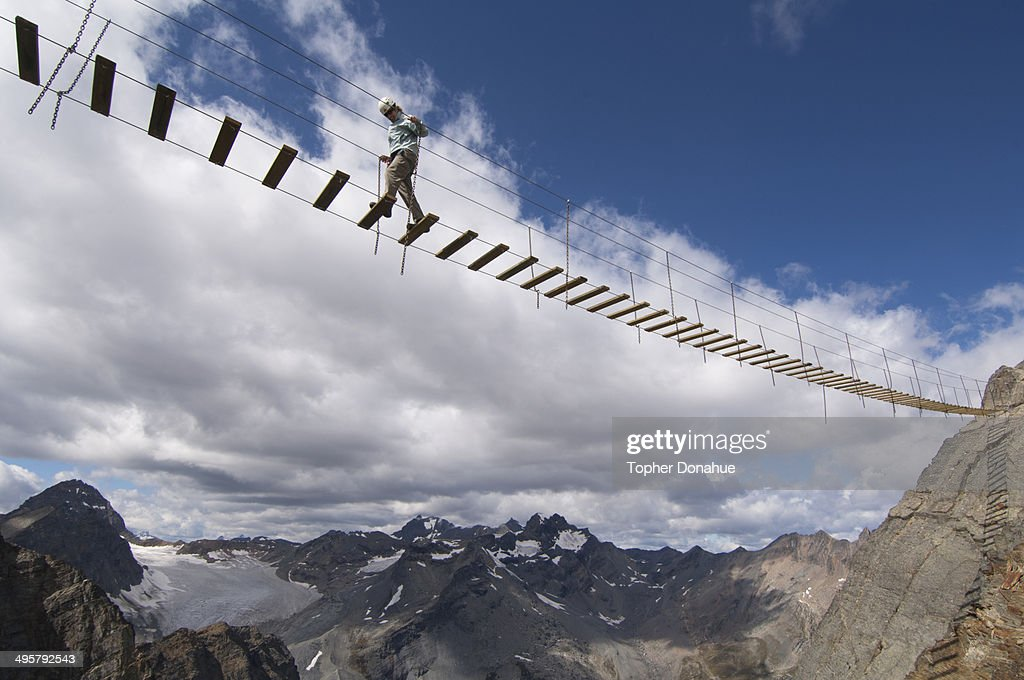 A woman crosses an exposed suspension bridge.