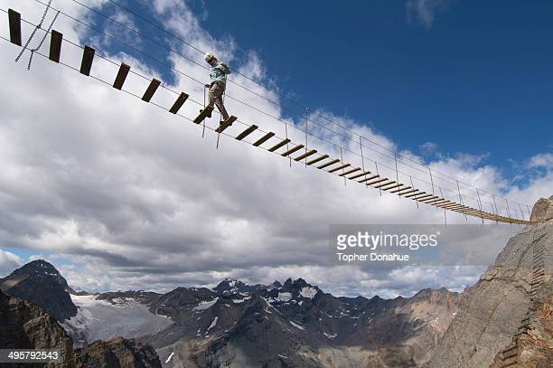 a woman crosses an exposed suspension bridge. - suspension bridge stock pictures, royalty-free photos & images
