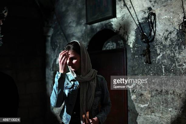 A woman crosses herself in the Church of the Holy Sepulchre on November 29 2014 in Jerusalem Israel The church is said to be where Jesus was...