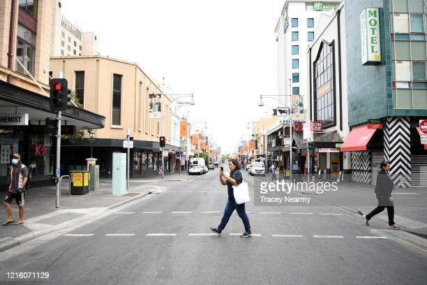 A woman crosses Hindley Street in Adelaide on April 01 2020 in Adelaide Australia The Australian government has introduced further restrictions on...