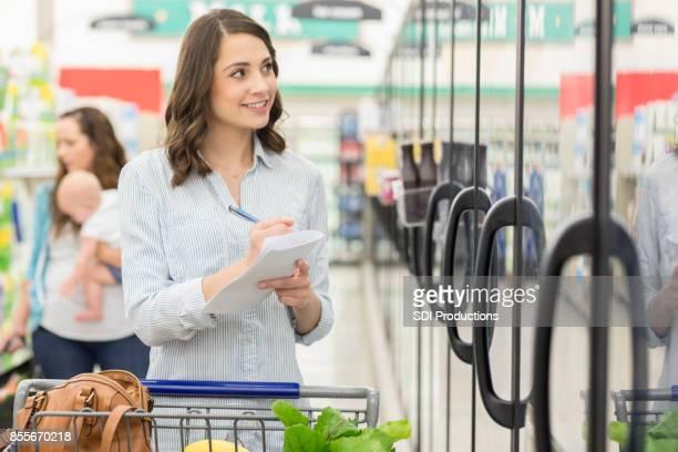 Woman crosses off items on her grocery list