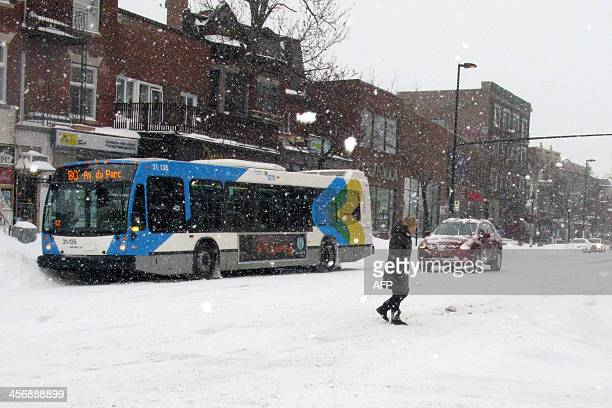 A woman crosses Park Avenue in Montreal on December 15 2013 as a powerful winter storm blew through eastern Canada with many flights cancelled or...