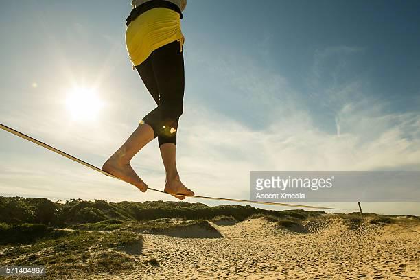 Woman crosses slackline above white sand beach
