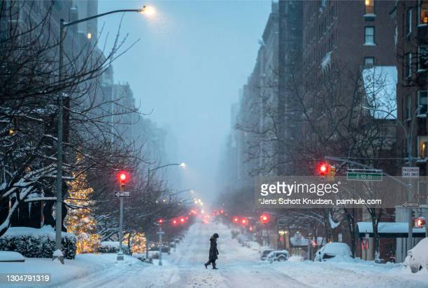 woman crosses street in new york city in the snow - manhattan new york city stock pictures, royalty-free photos & images