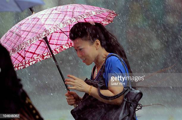 A woman crosses street trying to steady her umbrella against the rain in Taipei as Typhoon Fanapi hits eastern Taiwan on September 19 2010...
