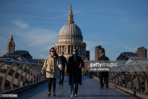 A woman crosses the millennium bridge in front of St Pauls Cathedral wearing a face mask for protection against the corona virus on March 16 2020 in...